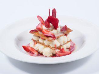 """מניפיק עלי בצק מקורמלים עם קרם וניל, רוטב שוקולד לבן, רוטב תותים ותותים טריים. צילום: יח""""צ"""