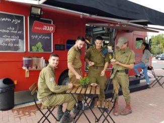 """משאית הפוד טראק של יכין פותחת שולחן לחיילים בעוטף. צילום: יח""""צ"""